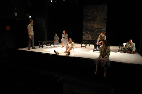 View from audience of actors all around the stage in various positions.