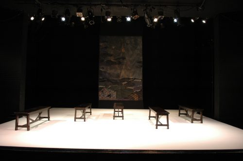 Empty stage with five parallel benches in full white light.