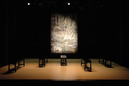 Tableau of stage with lit quilted backdrop and five benches staggered across the stage.