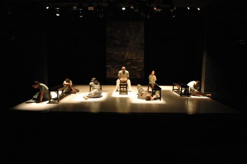 Tableau of cast at parallel benches under square-shaped spotlights isolating them.