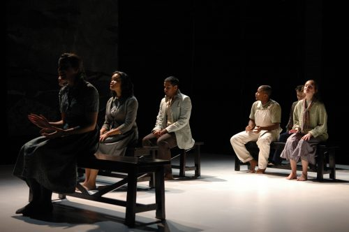 Angled view of cast singing on benches in rows, like on a bus.