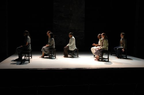Cast seated on benches in rows like on a bus, singing.