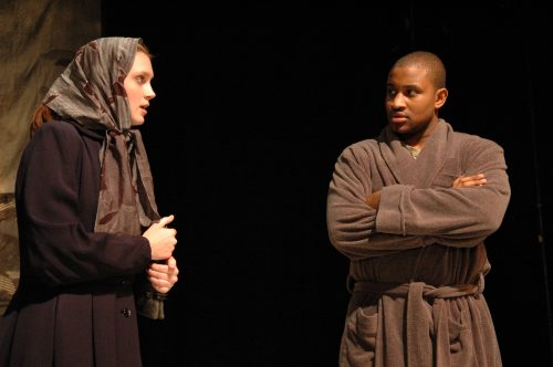 Man in bathrobe looking skeptically at nervous woman wrapped in headscarf and coat.