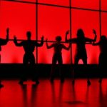 Dancers standing in silhouette.