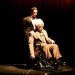 Butler wheeling out man in wheelchair.