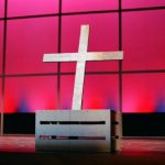 White cross in front of a pink backdrop.